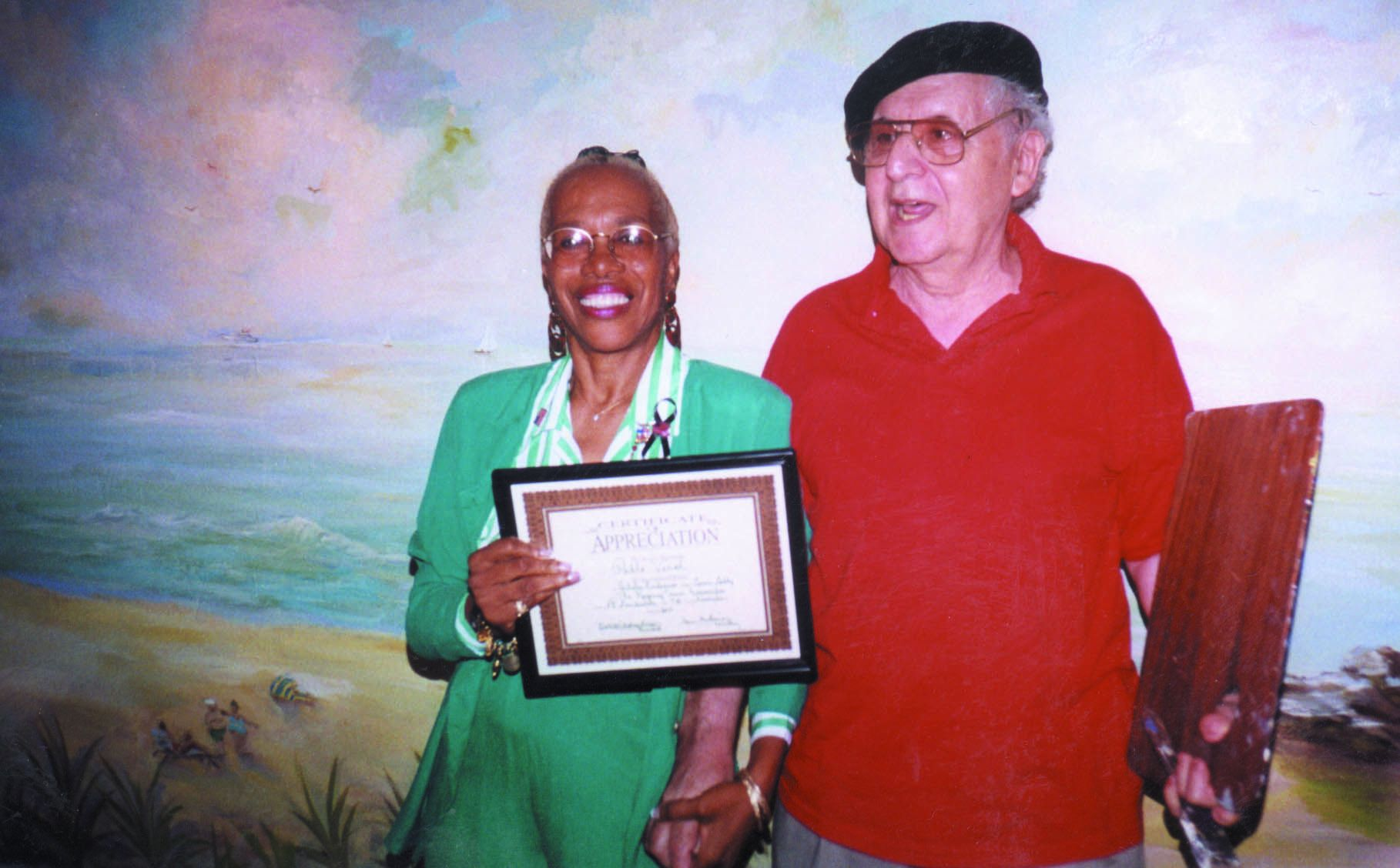 Regency Tower Board President Dott Nicholson-Brown Presents Board Member Pablo Verol with a Certificate of Appreciation while Standing before the Mural he Painted in the Garage Elevator Lobby